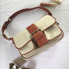 """Express shoulder bag Casual shoulder bag in EUC with lots of organizing details. Tan canvas body is accented with brown leather-like detailing. Snaps closed, front pockets zip. Measures 10"""" wide, 6"""" high, and 2.5"""" deep. Express Bags Shoulder Bags"""