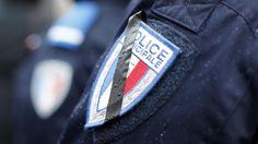 Dinsdag 13 januari 2015: Een Franse politieagent heeft met een stukje tape een rouwband gecreëerd op zijn insigne, tijdens de herdenkingsdienst van de drie agenten die zijn omgekomen bij de terreuraanslagen in Parijs.