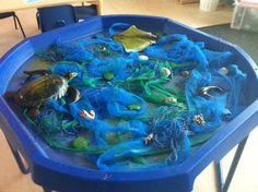 Sensory Play Under the Sea' – netting, blue voile fabric, green ribbons, shells, small world sea creatures, green glitter.
