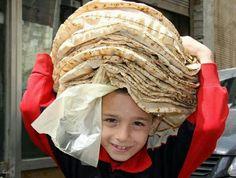 Syrian boy buying pita bread