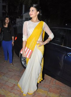 Jacqueline Fernandez wearing saree of sun shine yellow and creamish saree and Kate Spade book clutch