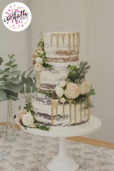Semi naked wedding cake with gold drips, fresh flower decoration with roses, eucalyptus and seed heads. Modern wedding cake design from The Confetti Cakery, image by The Confetti Cakery.