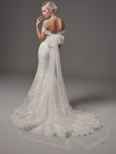 Sottero and Midgley - ADDISON, This fit-and-flare wedding dress features elegant lace motifs, a sweetheart neckline, and a striking hem. Finished with covered buttons over zipper and inner elastic closure. Detachable off-the-shoulder illusion sleeves, accented in lace appliqués, tie at the center back, creating a tulle train with lace edging (sold separately). Includes Belize satin belt.