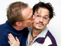 Johnny Depp receives a cheeky kiss from co-star Paul Bettany as they attend a photocall for the movie Transcendence.
