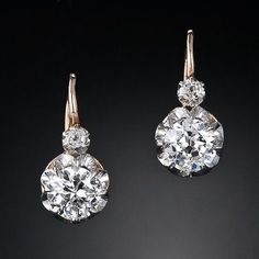Pair of antique diamond earrings from the turn-of-the-century. These earrings feature both an old European and old mine-cut diamond set in platinum over 18 karat yellow gold with a front clasping hinge. The diamonds drop just below the ear. French hallmarks, circa 1900.