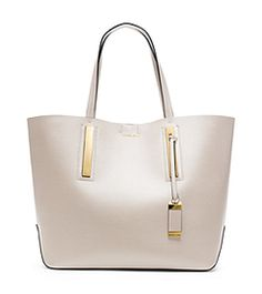 """""""I really thought about the convergence of a laid-back, relaxed sensibility with big city life,"""" says Michael. Designed in smooth leather with sleek, minimalist hardware, our Jaryn tote ups the ante on the elegance of an everyday carryall. An elongated shoulder strap allows for over the shoulder ease or you can let it dangle on your arm. Pair it with fall's tailored dresses and oversized sweaters."""