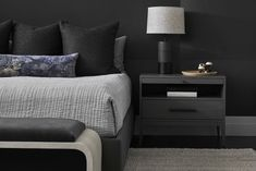 A dark and moody upholstered wall in this Master Bedroom sets the tone for a sultry, cozy space.