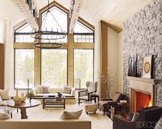 The great room of Collie and Greg Daily's Big Sky, Montana, home, which was designed by Ray Booth of McAlpine Booth & Ferrier Interiors. The sofa in front of the windows is by Christian Liaigre, the one at left is by John Saladino, the light fixture is by Paul Ferrante, and the mobile is by Noah Sheldon; a wood drying rack serves as a cocktail table, the wing chair is 19th century, and the cowhide rug is by Edelman Leather.