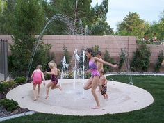 Splashpad -- a fun, safe, inexpensive (compared to a pool) water play option for your yard. The play area looks like stone, but it's actually a springy, spongy, recycled rubber material. No skinned knees on this surface.