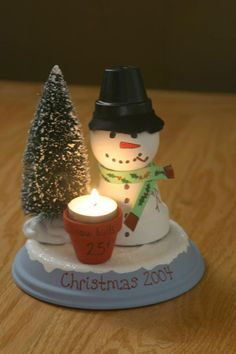 "bottom of pot, with upside down clay pot, Styrofoam head, battery operated ""candle"" in small pot, tree from christmas village....too cute!!"
