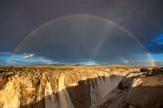 landscape photograph of a full rainbow over the augrabies waterfall