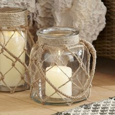 Infuse your outdoor space with rustic nautical charm with this jar-shaped glass lantern with criss-cross, netted jute accents. A sturdy rope handle lets y. Hurricane Lanterns, Candle Lanterns, Diy Candles, Candle Wax, Mason Jar Crafts, Mason Jar Diy, Coastal Style, Coastal Decor, Coastal Curtains