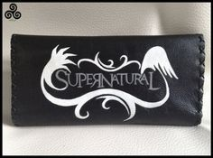 SUPERNATURAL......!Tobacco pouch in genuine black leather ... The designs are burnt with a pyrographer and painted with special colors for leather. Inside there are pockets for filters and papers, and closes with magnetic buttons.  Dimensions: 155mm x 200mm.