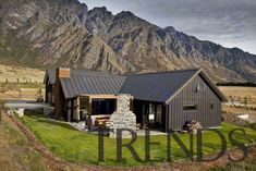 Exterior view of house with dark walls and cottage, elevation, farmhouse, home, house, hut, landscape, log cabin, mountain, mountain range, property, real estate, roof, siding, brown, gray