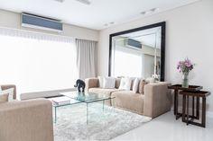 Living con sillones enfrentados y mesas ratonas de vidrio. Alfombra y espejo de pie con diseño de biseles. Mesas encastrables como mesas de arrime.