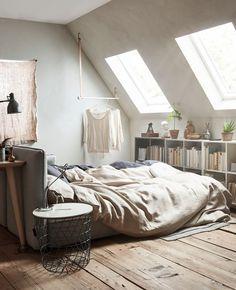 Et ekstrarom med skråtak og møbler i nøytrale farger, blant annet en sovesofa og et skrivebord.