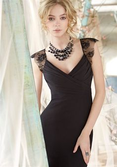 Black chiffon A-line bridesmaid gown, cross over draped V-neckline, empire bodice Black Chantilly lace cap sleeve and covered back.