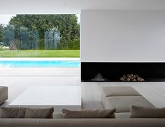 Large windows and fireplace in white living room by Pascal Bilquin and Minus