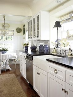 Cottage Galley -- This white galley kitchen has a pretty, country look. Classic white cabinets reflect light from the windows, making the room feel bigger. A raised ceiling adds visual volume and prevents the space from feeling cramped. A small wicker dining set contributes to the casual ambience.
