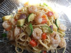 Shrimp and Veggie Pasta   1 lb. 41-60 count peeled and deveined shrimp  1/2 lb. thin spaghetti (use more if you want a little more pasta)  1 large zucchini, cut into chunks  1 medium red onion, chopped  1 medium red bell pepper, chopped  2 cloves garlic, minced  1 T. olive oil  2 T. unsalted butter  1/2 C. heavy cream  1 tsp. Italian seasoning  3 T. grated Asiago cheese, plus a little more for serving  pinch of salt and pepper   Cook pasta according to package directions. Meanwhile, heat ...