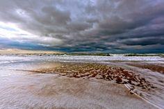 donkere wolken boven strand en zee