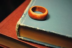 I make these rings out of balsa wood and stain them with a cherry wood stain. To make one, I drill out a piece of wood and get the exact size with a dremel tool. I then shape the wood with the dremel and sand the ring (down from 60 gauge to 240 gauge sandpaper). The ring is then stained with one to two coats of stain and sealed with satin polyurethane.