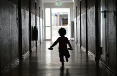 A child runs through a hallway in a refugee center in the town of Giessen, in...