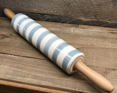 This is a brand new Rae Dunnstoneware rolling pin with wooden handles and blue stripes on the roller. It is a must-have addition to any and all Rae Dunn collec