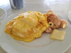 Teddy bear sleeping -- from what I can see, made of scrambled eggs, rice, and cheese slice