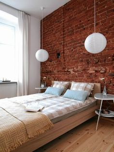 MIESZKANIE. Proste łóżko z płyty meblowej imitującej drewno brzozy pasuje do ceglanej ściany. W oknie wiszą zasłony z lnu. W ceglanej ścianie celowo nie wypełniono ubytków i szczelin po kablach. Dzięki temu wygląda naturalnie, a w zagłębieniach można ustawić dekoracyjne drobiazgi.