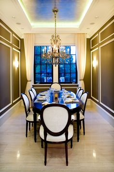 Custom Italian dining table and chairs with high contrast wall paneling.