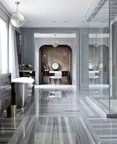 Those floors! Stunning bathroom with seamless glass shower, marble tiles floor, Waterworks Engine Turned Pewter Oval Waste Can, Waterworks Candide Freestanding Oval Cast Iron Bathtub, gray silk curtains, arched vanity nook, espresso stained vanity and blue walls paint color. | decorpad