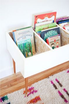 Keep Kids Organized and Curious With This DIY Book Bin Katie Loves …this functional and fashionable book bin for a kids bedroom or playroom. A set of mid century modern table legs and beautiful wallpaper make this version stand out.