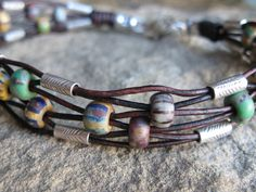 Rustic 6-strand leather bracelet with Czech glass beads and Hill Tribes silver tubes.  Pretty woven effect.  #handmade #jewelry #beading