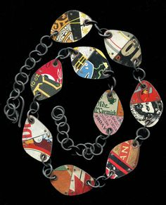 FoFum Necklace ||  Nine pieced tin charms with tube rivets and steel chain combine to make this awesome necklace. Juxtapositions make for interesting graphic quality. About a ten inch drop on the body, this piece measures 28 inches end to end.  $ 100.00