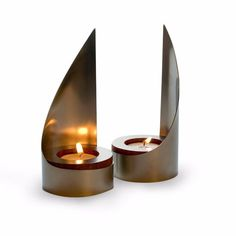 Satin nickel and mahogany #candle holders, based on a design commissioned by the Maltz Museum of Jewish Heritage. The backs stretch outwards like tiny sails and are hand-buffed to reflect the light of the candles into the room, adding a warm glow to any #Sabbath.