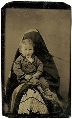 "This is a really creepy image but the rational behind it was that photographs were really expensive, so mothers got their children to sit on their laps so the child didn't move and they draped themselves in black cloth so that they weren't actually ""in"" the photograph - Just a bit of history for you Anet & Alexa"