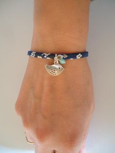 Ce bracelet est composé dun ruban Liberty bleu avec une breloque argentée qui représente un oiseau et une perle de verre bleue.  Grâce à sa