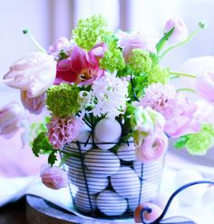 Eggcelent idea  A wire egg basket is a clever container for a floral bouquet. Place glass of water in the center of the basket and surround it by eggs.  You can use dyed or plain white.  Add the flowers in to the center 'vase' and you have a charming centerpiece!