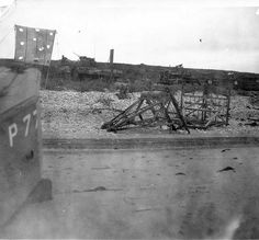 "Omaha Beach, showing wreckage. Note ""D"" marker on poles, erected to guide incoming ships to proper destination"