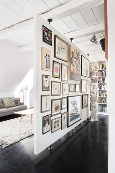 Love this idea of defining 2 spaces with a floating partition filled with art & photos. Have no extra walls? Create one! #art