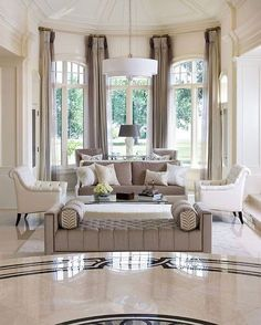 natural light through floor to ceiling boy windows for neutral beige and white living room