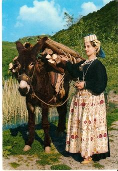 Europe | Portait of a woman wearing traditional clothes and a donkey, Scanno, province of L'Aquila, Abruzzo region, Central Italy