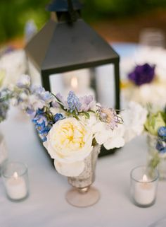 Iron lantern and blue, purple and yellow flower centerpiece. Photo by Justin DeMutiis Photography