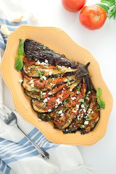 A delicious Mediterranean eggplant recipe with tomatoes, garlic and crumbled feta. It tastes amazing and would make any eggplant hater into an eggplant lover.