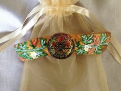 Green, gold, and rose are the primary colors of this barrette which is actually a piece of wearable art. The barrette is made from a dried gourd. Design by Happy Hummer Art
