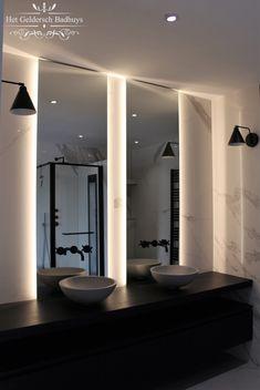 Hier ziet u een deel van een chique moderne badkamer. De badkamertegels zijn van marmer. Het badmeubel is zwart en heeft 2 onderlades, ideaal voor om uw spullen kwijt te kunnen! De spiegels zijn maatwerk met LED-verlichting. De inbouwkranen komen uit de muur, vanuit de spiegel.