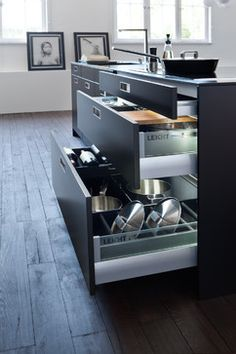 Concealed behind large-surface tall units is a perfect kitchen arrangement: electric appliances behind slide-away doors, ready for easy use, along with crockery, pots and pans.