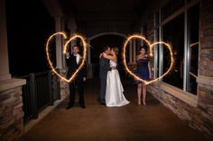 This is a great bride and groom image with the best man and maid of honor making hearts. By Robert Holley Photography