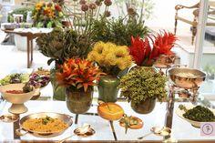 arranjos altos com bromélias, flor de alho, repolho ornamental, proteas e ligustros, em tons de laranja, vermelho, amarelo e verde, salpicados de lilás.